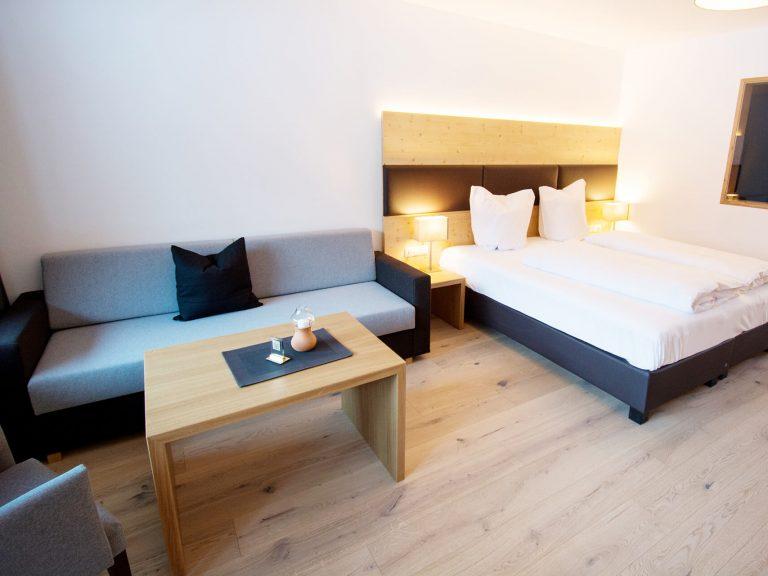 Eine Couch neben einem Doppelbett in einem der Appartements im DER SONNENHANG