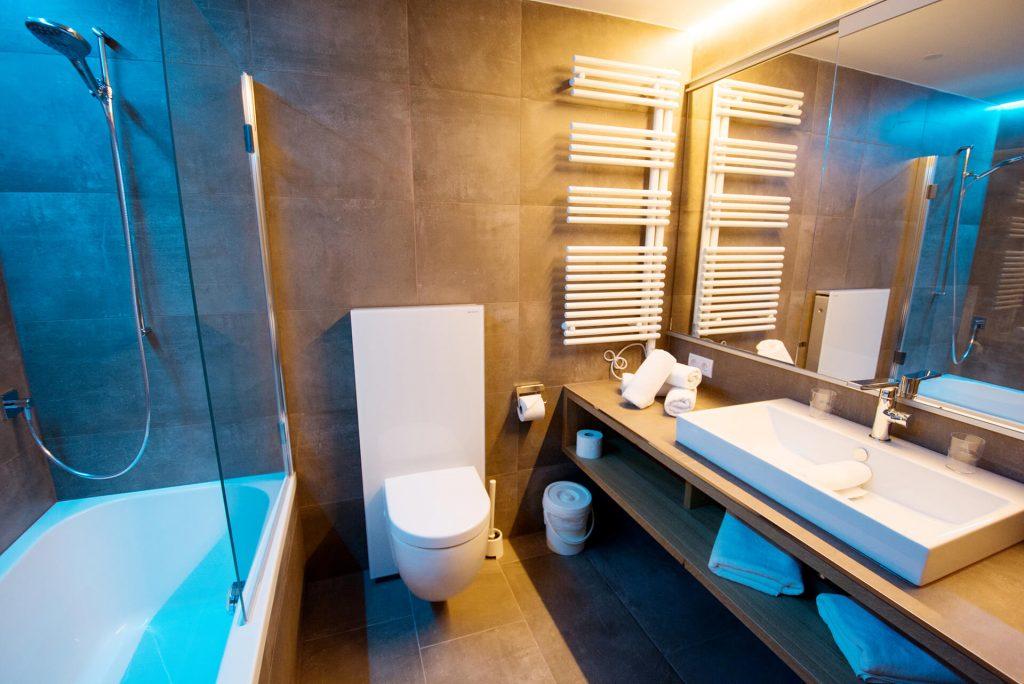Der Blick in ein Badezimmer mit Waschbecken, Badewanne und WC