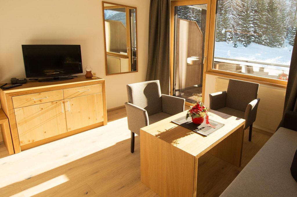 Wohnzimmer mit zwei Stühlen, einem Tisch sowie einem Fernseher.