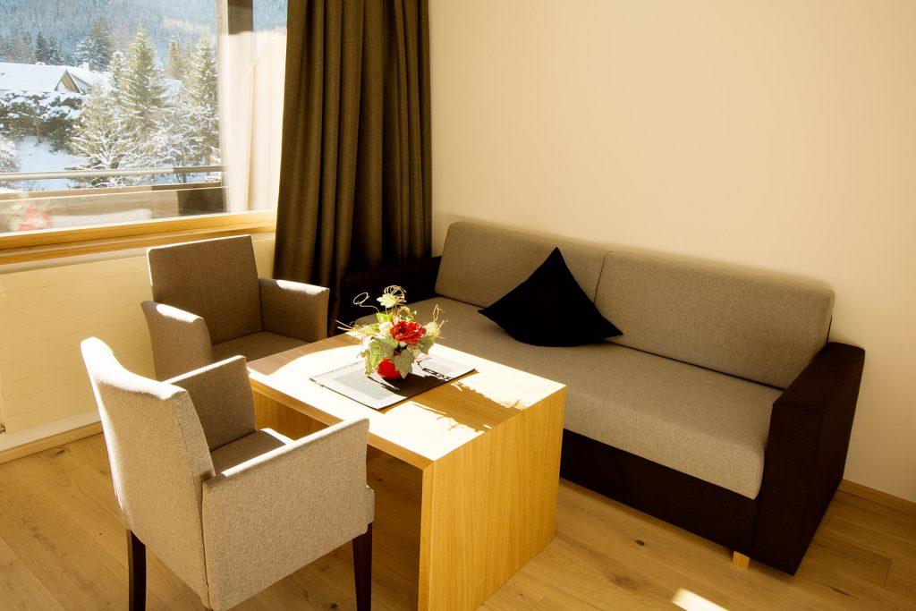 Eine gemütliche Couch mit zwei Sesseln und einem Tisch.