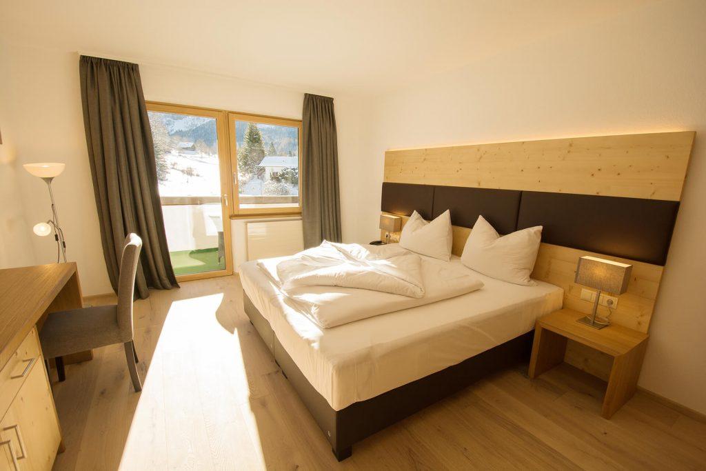 Ein Doppelbett in einem der Appartements im DER SONNENHANG