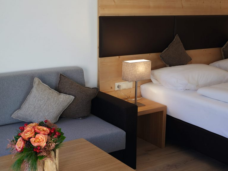Zimmer mit Doppelbett, moderner Sitzecke, Blumenschmuck am Couchtisch.