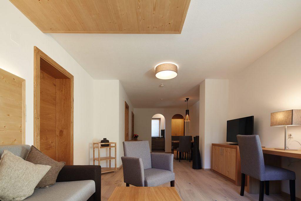 Großzügiger Wohnraum mit Sofa, Sessel, Schreibtisch und Stuhl, TV, Essecke, helles, freundliches Ambiente.