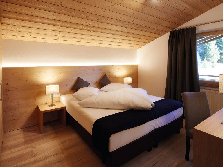 Schlafzimmer mit viel Holz, mit Doppelbett, kleiner Schreibtisch mit Stuhl, Kasten links im Bild. Zimmer unter der Dachschräge.