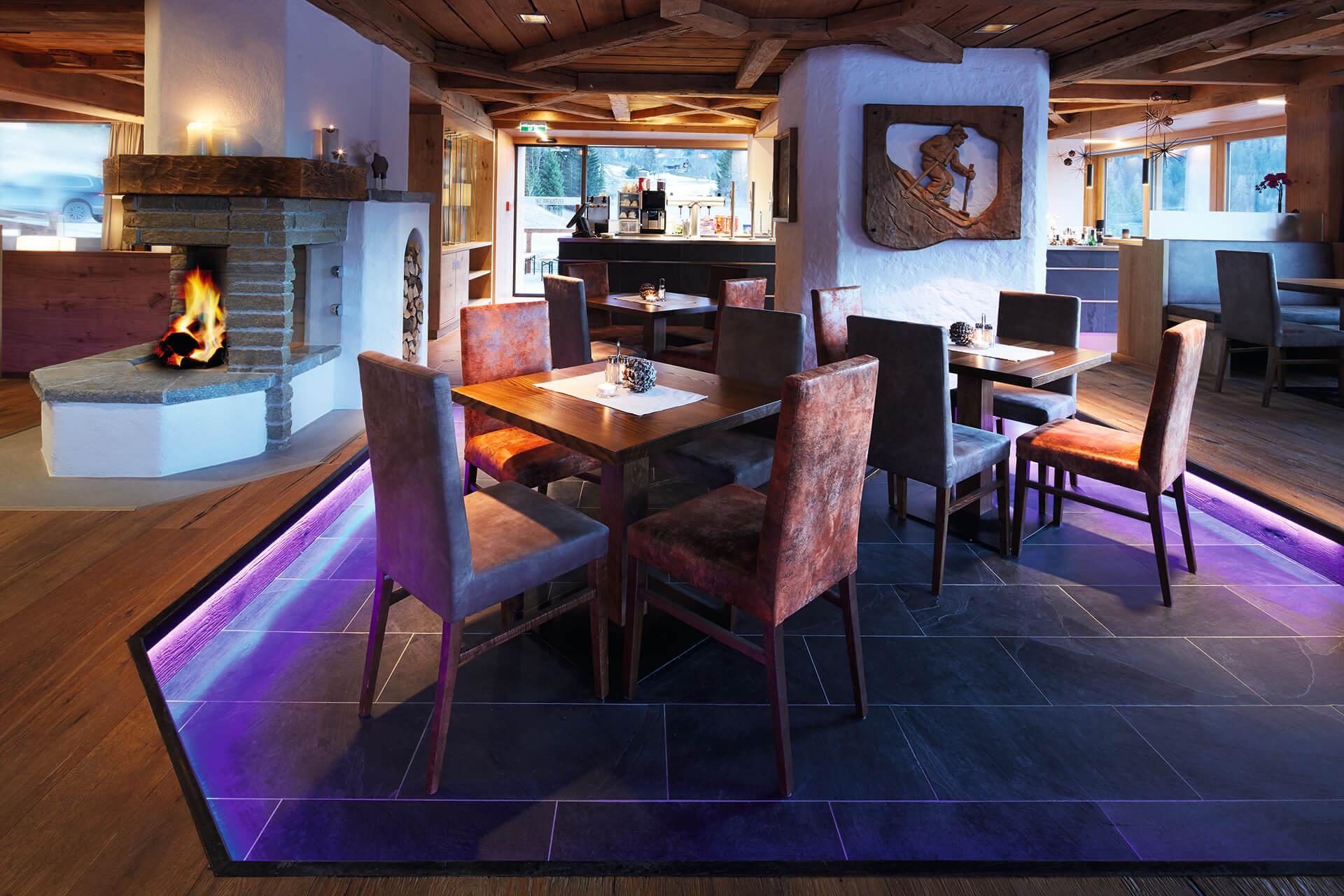Tische und Stühle im Restaurant. Links im Bild ist ein Feuer im Kamin zu sehen. alpin-modernes Ambiente.