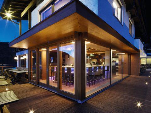 Außenansicht der Bar, Bild von Terrasse aufgenommen, am Abend, beleuchtet.