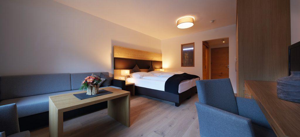 Appartement mit Wohn-Schlafraum mit Doppelbett, Sofa, Couchtisch, Schreibtisch, Sessel, Kastenfront und im Hintergrund Eingangsbereich und Zimmertüre.