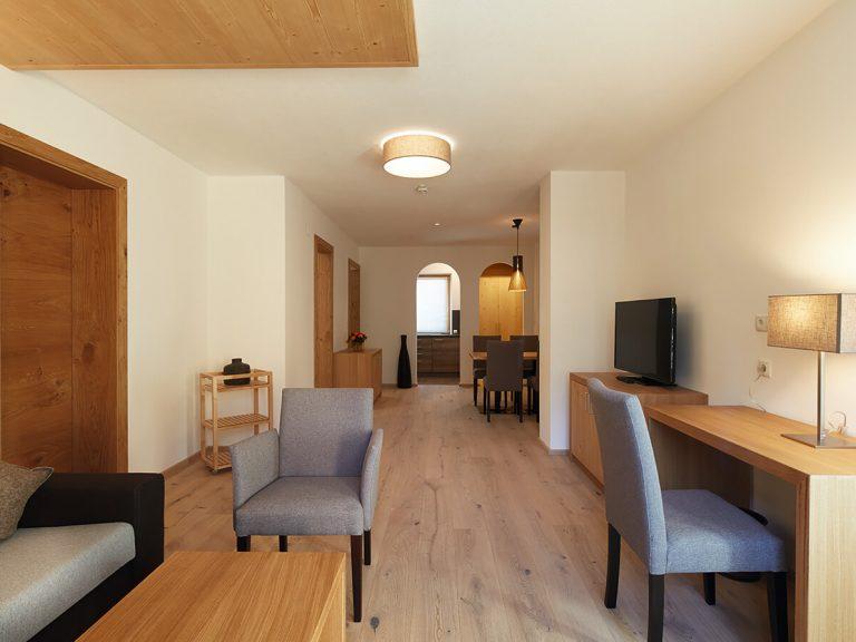 Großer Wohnraum eines Appartements mit Sofa, Sessel, Schreibtisch und Stuhl. TV, Essecke, im Hintergrund der Eingang zur Küche. helle, freundliche Farben.