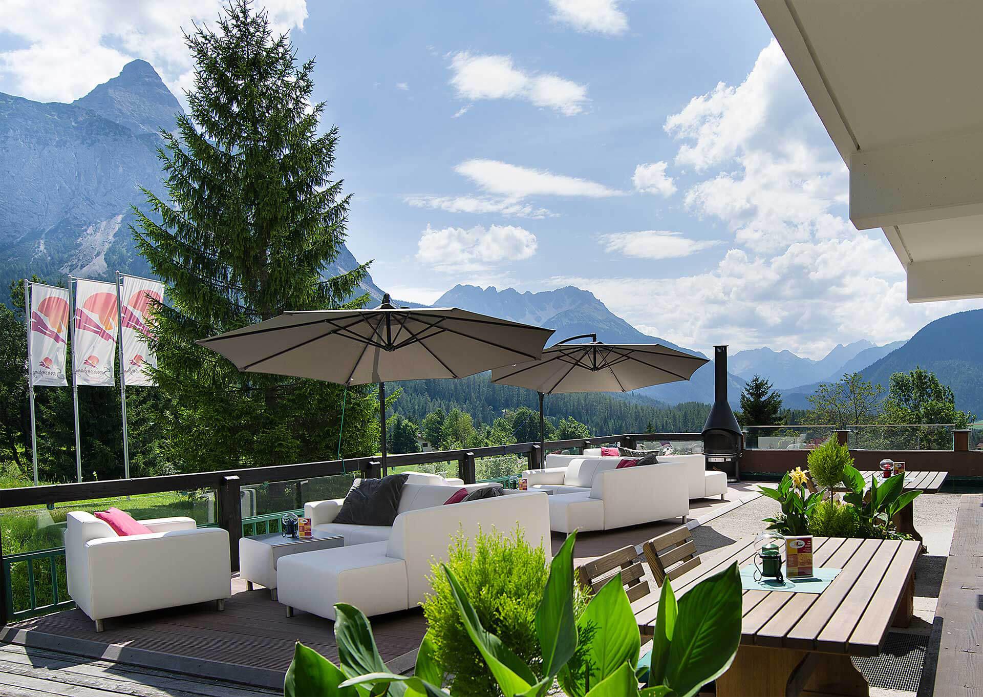 Sonnenterrasse mit Sitzgelegenheiten und Esstischen. 2 Sonnenschirme sind aufgespannt. im Hintergrund Berge und Grün.